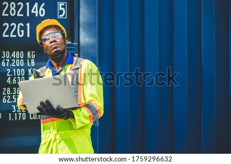 Black African worker working in logistic shipping using laptop to control loading containers at port cargo for import export goods foreman looking high for future Stock fotó ©