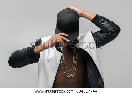 Black afroamerican rebellious rapper on grey background. Closed face, rejection, separated, reluctance to see, breaking off. Ghetto, challenge to society, cheeky, cool Stock fotó ©