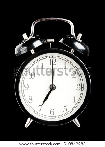 Black alarm clock seven o clock isolated on black.