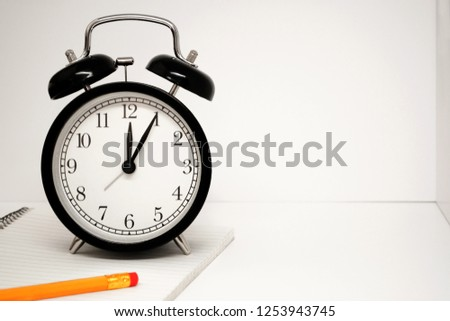 Black alarm clock with white dial and yellow pencil on a white notepad on a spiral in a spase as white background #1253943745