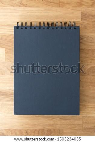 Black album, sketchbook on wooden background