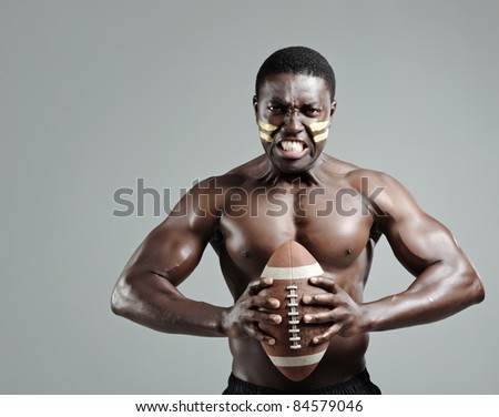 Black american football sportsman gripping a ball in studio