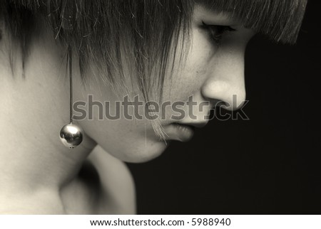 Black&white close-up shot of girls silver earring - stock photo