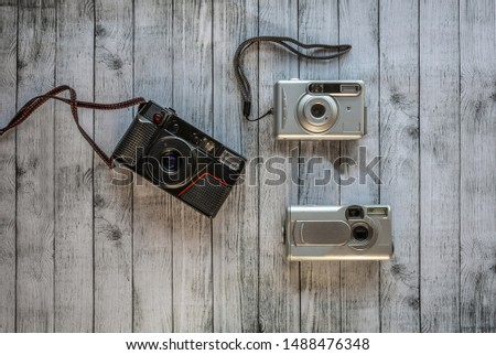 Black analog camera and two old small digital cameras placed on a grayish wooden surface #1488476348