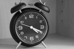 Black analog old alarm clock set for early morning at 4:20. Twenty minutes after four.