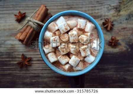 Black and blue cup of hot cocoa with marshmallows, star anise and cinnamon