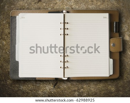 Black and brown leather cover of binder notebook on stone