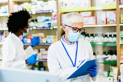 Black and Caucasian professional pharmacists working in modern drugstore. They are wearing face protective masks and shield for protection from virus disease. Coronavirus, Covid-19 concept.