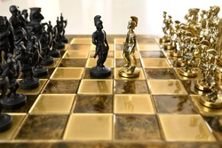 Black and gold metal Roman centurion chess figurines from opposing armies on chessboard ready for battle