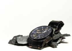 Black and gold wristwatch on top of dark rocks on a white background