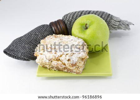 Black and gray woven napkin placed with freshly baked crumb cake and green apple on square, green dish
