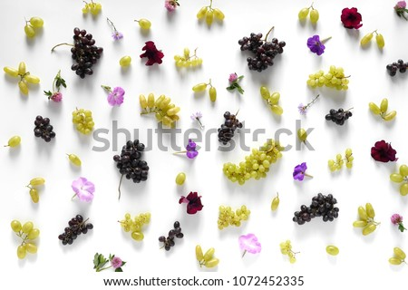 Black and green grapes, lilac flowers on a white background. The pattern of grapes of different varieties, top view. Food background. #1072452335