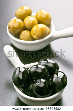 black and green olives in design bowl sprinkled with oil, on glossy dark background