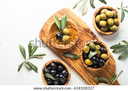 Black and green olives in wooden bowls and olive oil bottle. Top view on white background with space for text.