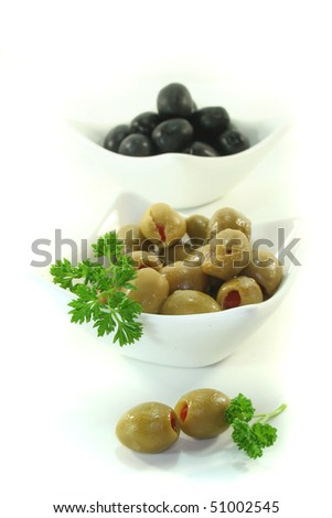 black and green olives with parsley on a white background
