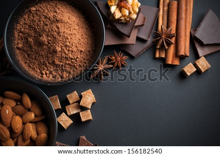Black and milk chocolate, cocoa powder, nuts, sweets, spices and brown sugar on a black background, food concept