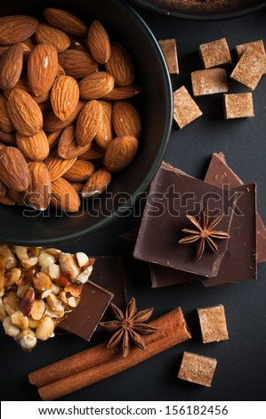 Black and milk chocolate, nuts, sweets, spices and brown sugar on a black background, food concept