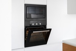 Black and modern built in oven with open glass door on white contemporary kitchen