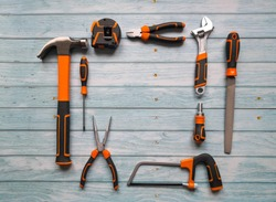 Black and orange construction tools aligned in a square shape on blue background shot from above.Top view, flat lay. Construction, repair, production and DIY concept.