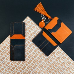 Black and orange stylish leather purse for driver's license, passport or id card. Documents cover and holder. Near ginger trinket for keys. Flat lay. Trendy accessories concept. Patterned background.