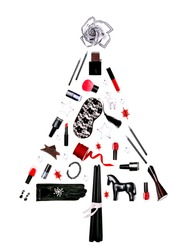 Black and red feminine accessories and cosmetics laid out as a Christmas tree on white background creating winter holiday atmosphere. Gifts for her. Flat lay, top view.