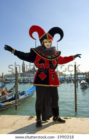 Black and red jester in front of gondolas on Grand Canal,Venice,Italy