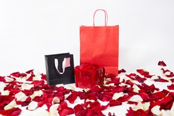 Black and red kraft paper shopping bags and gift box with bow isolated with red rose petals on white background. Valentine's day gifts.Holiday shopping.Valentine's day sales
