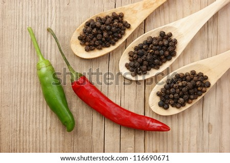 Black and red pepper in wooden spoon on the old board