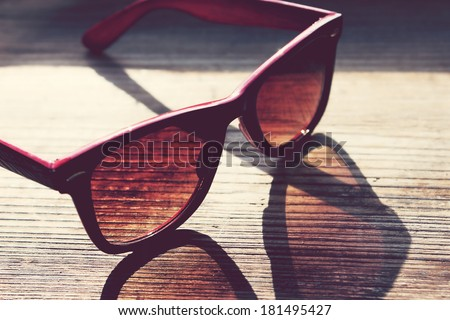 Black and red vintage sunglasses on a wooden table closeup