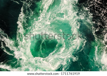 Photo of  Black and turquoise swirling water of the Saltstraumen Maelstrom in Bodo, Norway. Saltstraumen has one of the strongest tidal currents in the world