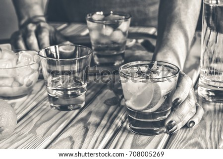black and white. A young girl is preparing an alcoholic or non-alcoholic cocktail. hands, bartender, bar, restaurant, mint, lime, lemon, alcoholic, non-alcoholic