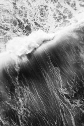 Black and white aerial view of a breaking wave, on a big swell day in france, lots of whitewater and energy