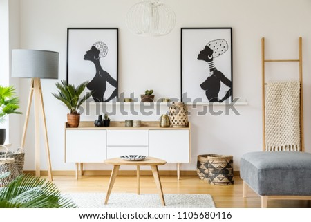 Black and white african posters above cabinet in living room interior with lamp and table. Real photo