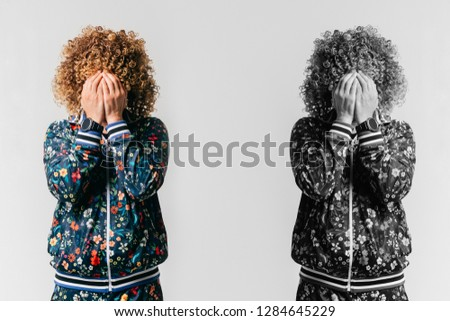 Black and white and color portrait of unrecognizble unhappy depressed man with face hidden by hands standing on white background beyond his alter ego. Self reflection. Afro male in tracksuit crying