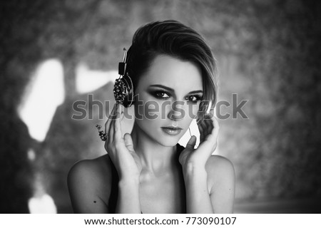 Stock Photo Black and white art monochrome photography. Lovely girl with tanned skin and white hair listening to music on headphones.