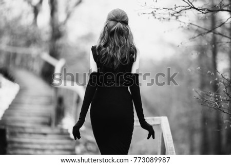 Black and white art monochrome photography. Striking girl with long hair in black clothes. A woman in a black dress and jacket. Beautiful elegant model