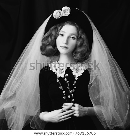 Stock Photo Black and white art monochrome photography. Victorian woman with long braids with an unusual appearance in a black dress