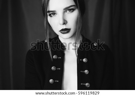 Stock Photo Black and white art photography monochrome, beautiful girl in black unbuttoned jacket with red lips on dark background looking at the camera. Fashion photography. Bright appearance.