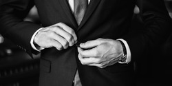 black and white art photography monochrome, correct button on jacket, hands close-up, dressing, man's style, stylish man, grayscale