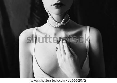 Stock Photo Black and white art photography monochrome, pearl necklace on the pale neck on a black background. Woman with long nails manicured. Scarlet lipstick on lips of a young girl. Pronounced collarbone.
