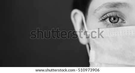 Stock Photo black and white art photography monochrome, red-haired girl with a medical mask on a red background, woman doctor, woman with intense look, European, half of the face, hair pinned