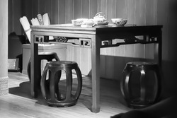 Black and white Artistic atmosphere image background of classic traditional Chinese culture dining room with small space wooden table chair wall and floor.