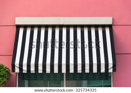 black and white Awning over glass window on pink wall #325734335