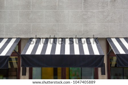 black and white awning over the glass window of shop, canvas shading decoration for coffee shop #1047405889