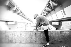 black and white back view of young sportsman in sweatshirt  man is tying shoelace of sneakers, the bridge architecture , urban landscape, beautiful cityscape with young guy in hoodie with copy space