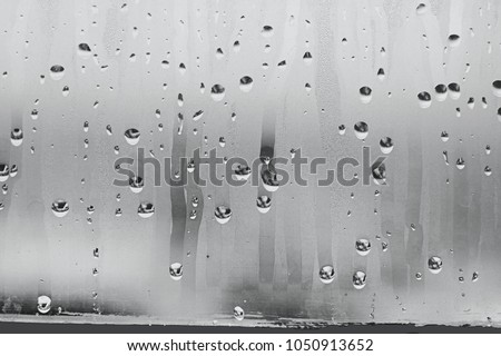 Black and white background of the condensate flowing water on the window glass. Collecting and streaming down. High air strong humidity, large drops drip