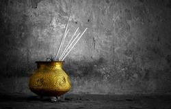 black and white background with a golden bowl with  incense