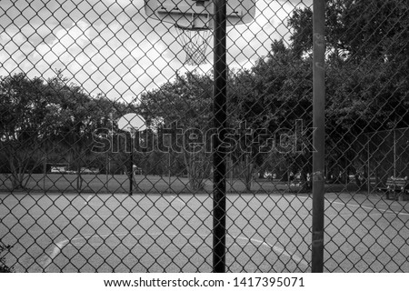 Black and white basketball court from behind fence #1417395071