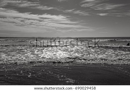 Black and white beach with silhouettes of people at Port Macquarie Australia. Beautiful Australian beach on the pacific ocean. View towards sea on a sunny day. #690029458