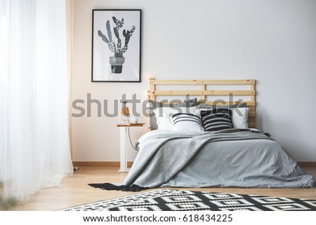 Black and white bedroom with grey accessories, big window and cactus poster #618434225